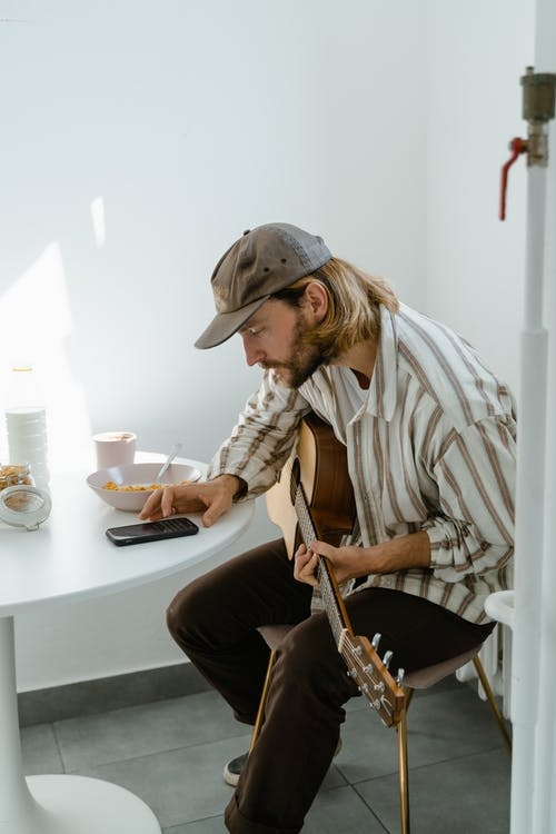Man in White and Brown Stripe Dress Shirt Playing Guitar
