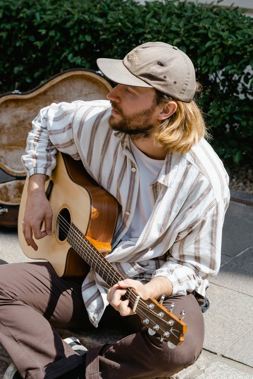 Man in White and Brown Plaid Dress Shirt Playing Acoustic Guitar