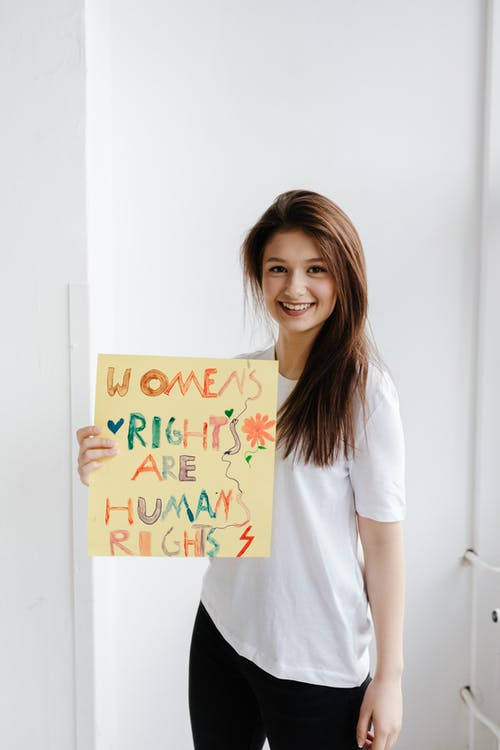 Woman in White Crew Neck T-shirt Holding a Poster