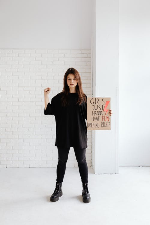 Woman in Black Shirt and Black Pants Holding a Poster