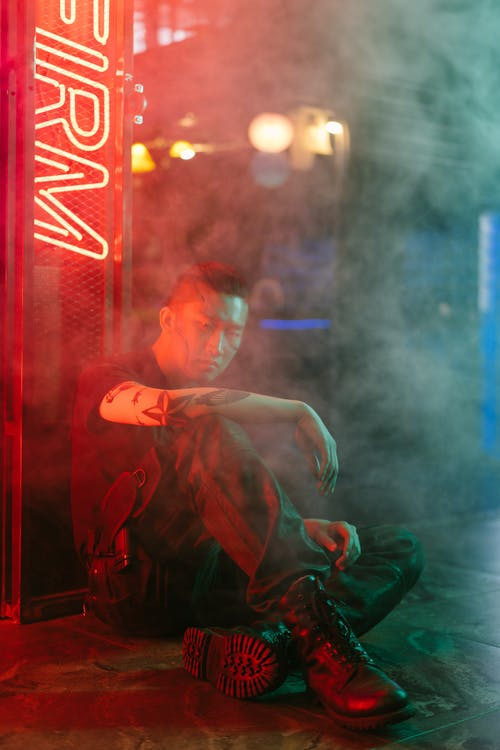 Man Sitting on the Floor Beside a Neon Signage