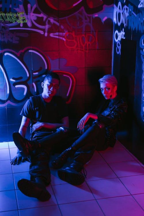 Man in Black Shirt Sitting Beside Woman in Black Shirt