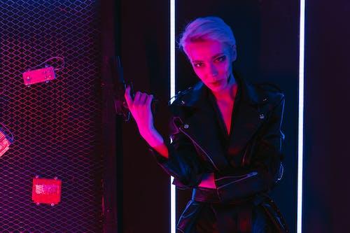 Woman in Black Jacket Holding a Gun