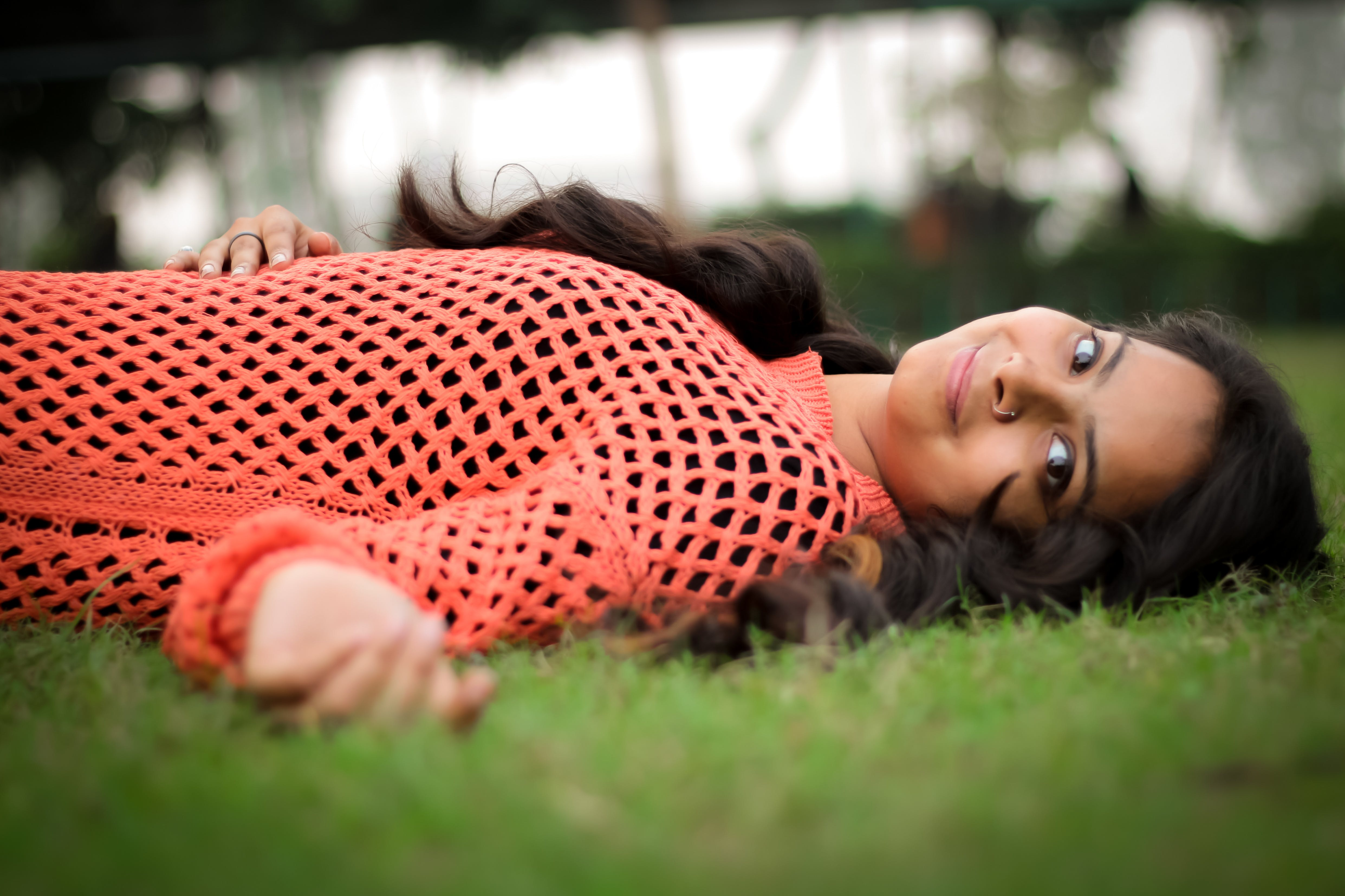 Photo Woman in Orange Long-sleeved Shirt Laying on Lawn
