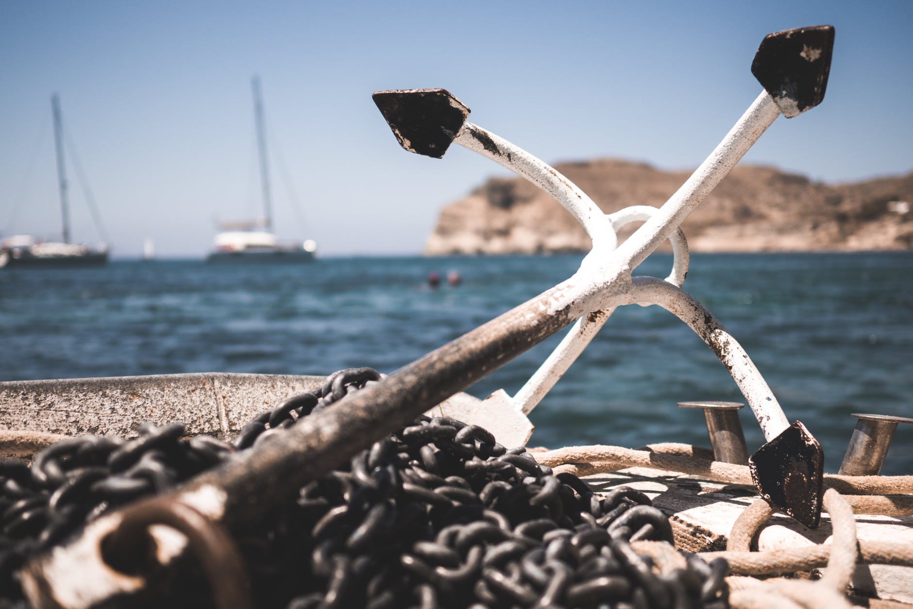a rusty boat anchor by the shore