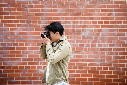 Man in Beige Jacket Holding Black Dslr Camera