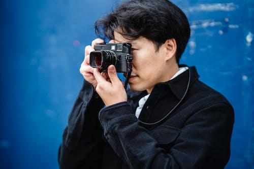 Man in Black Suit Jacket Holding Black Dslr Camera