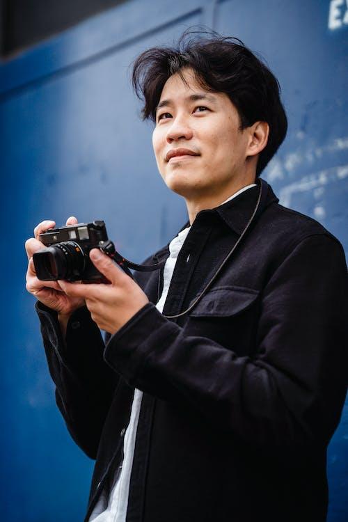 Man in Black Suit Holding Black Dslr Camera