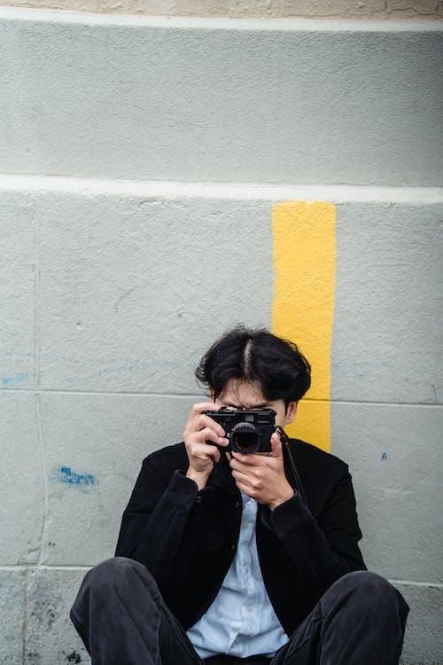 Man in Black Jacket Holding Black Camera