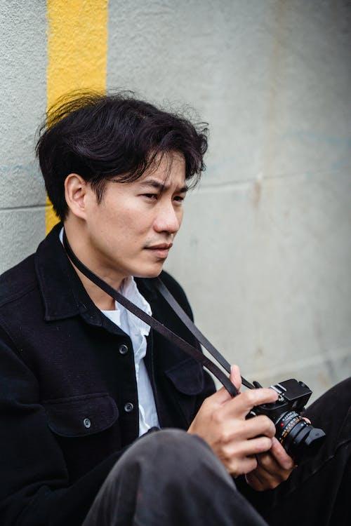 Man in Black Coat Holding Black Smartphone