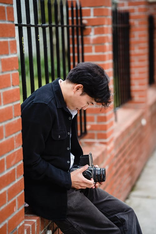 Man in Black Dress Shirt Holding Black Dslr Camera