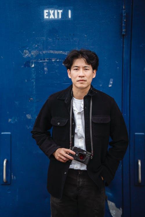 Man in Black Jacket Standing Beside Blue Wall