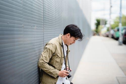 Man in Brown Coat Holding Black Smartphone