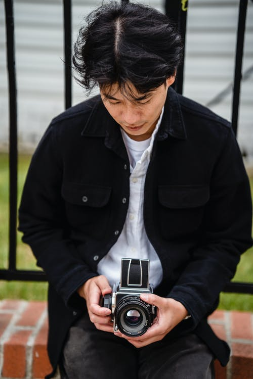 Man in Black Suit Holding Black and Silver Camera
