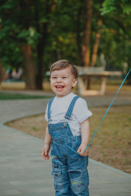Content toddler kid with brown hair laughing while looking forward on walkway in park on blurred background