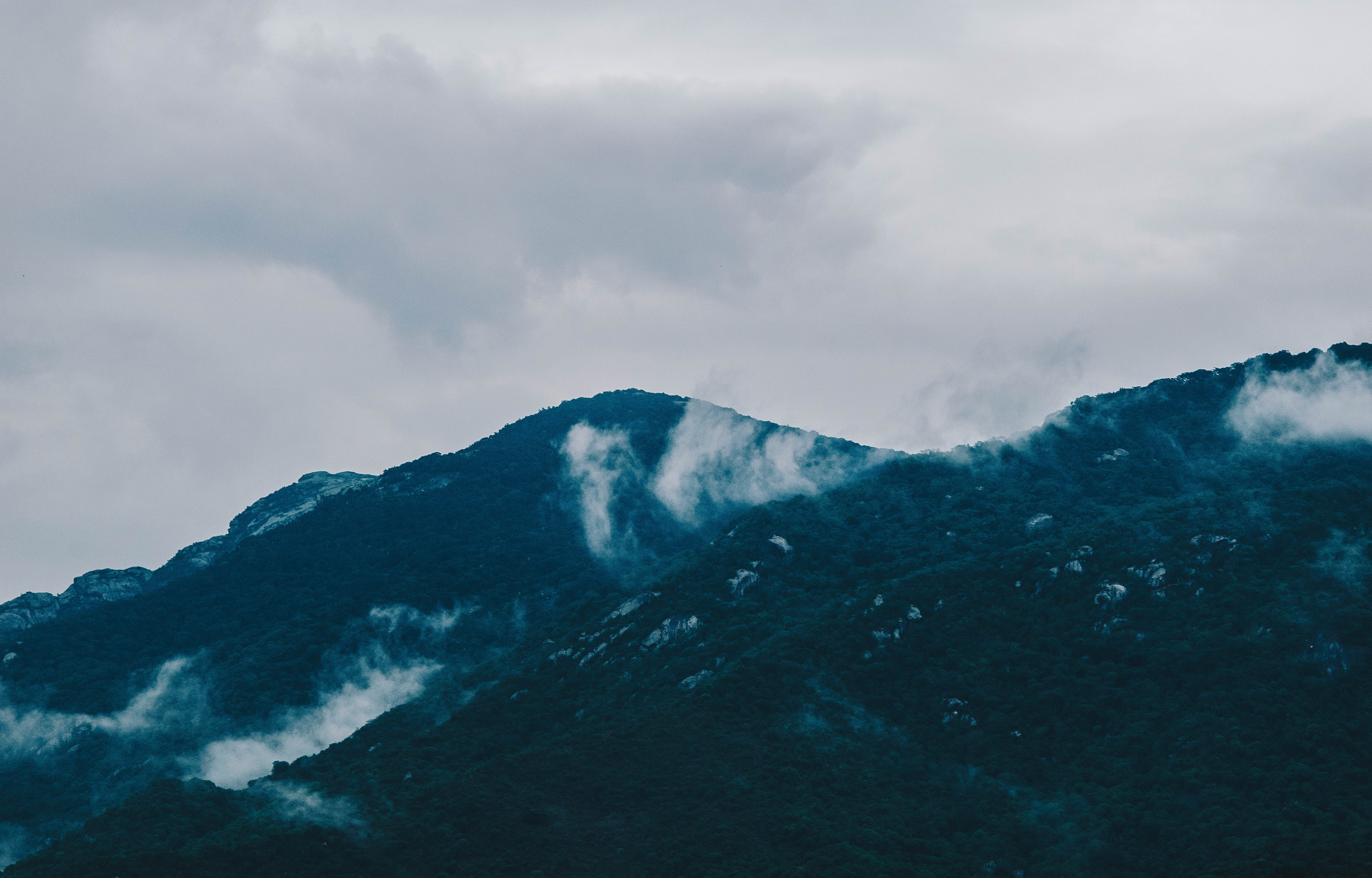 Photography of Mountain Under Cloudy Sky