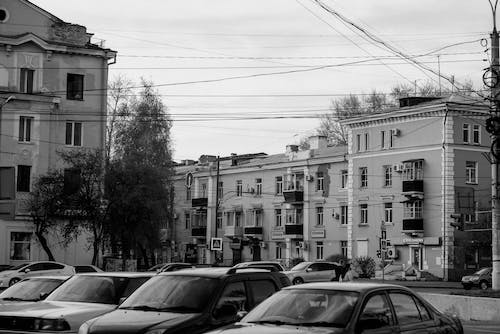 Grayscale Photo of Cars Parked Near Buildings