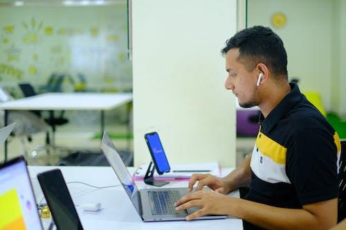 Man in White and Yellow Shirt Using Macbook Pro