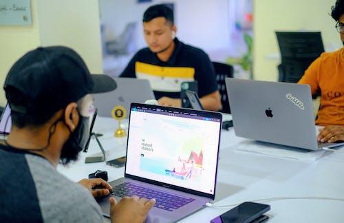 Man in Gray Jacket Using Macbook Pro