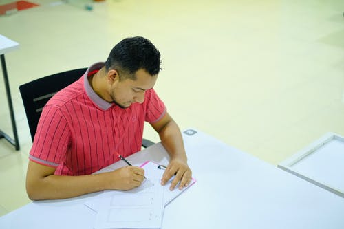 Man in Red and White Striped Crew Neck T-shirt Writing on White Paper
