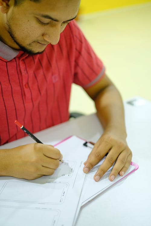 Man in Red Crew Neck T-shirt Writing on White Paper