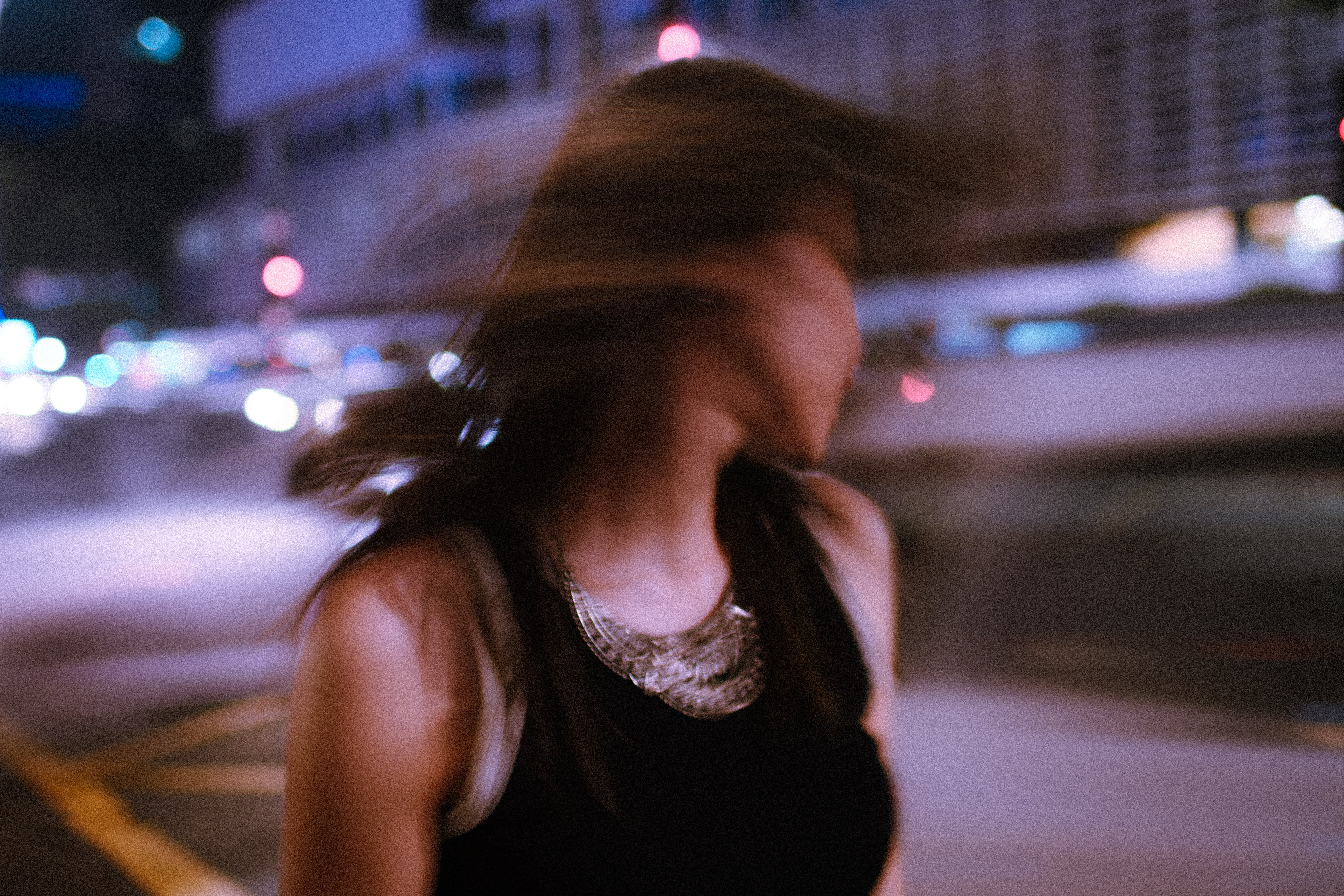 Tilt Shift Photography of Woman Wearing Tank Top during Nighttime