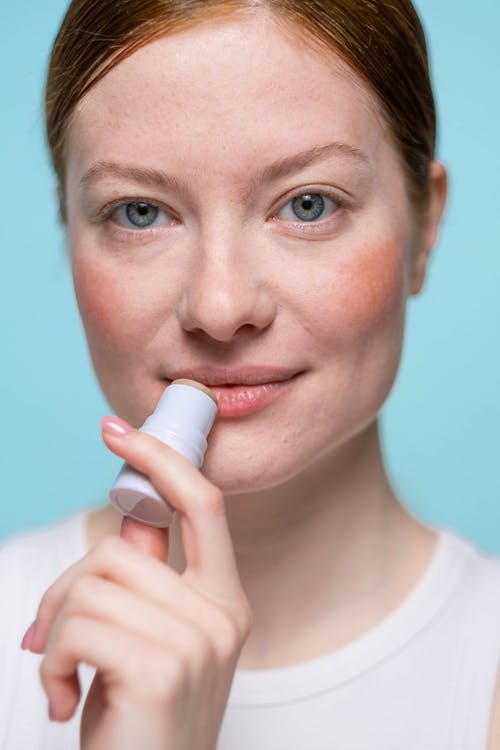 Woman With Blue Eyes Holding White Plastic Bottle
