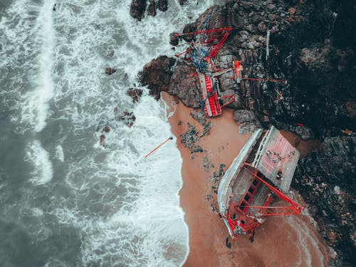 Red Boat Crashed on Rocky Seashore