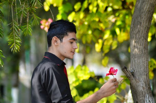Man in Black Shirt Holding Red Petaled Flower