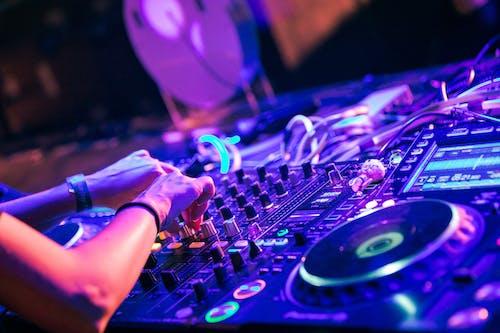 Person Turning Knobs on DJ Digital Mixer Deck
