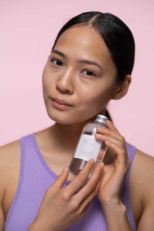 Woman in Purple Tank Top Holding White Bottle