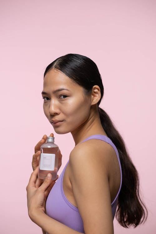Woman in Purple Tank Top Holding Bottle Of Facial Tonic