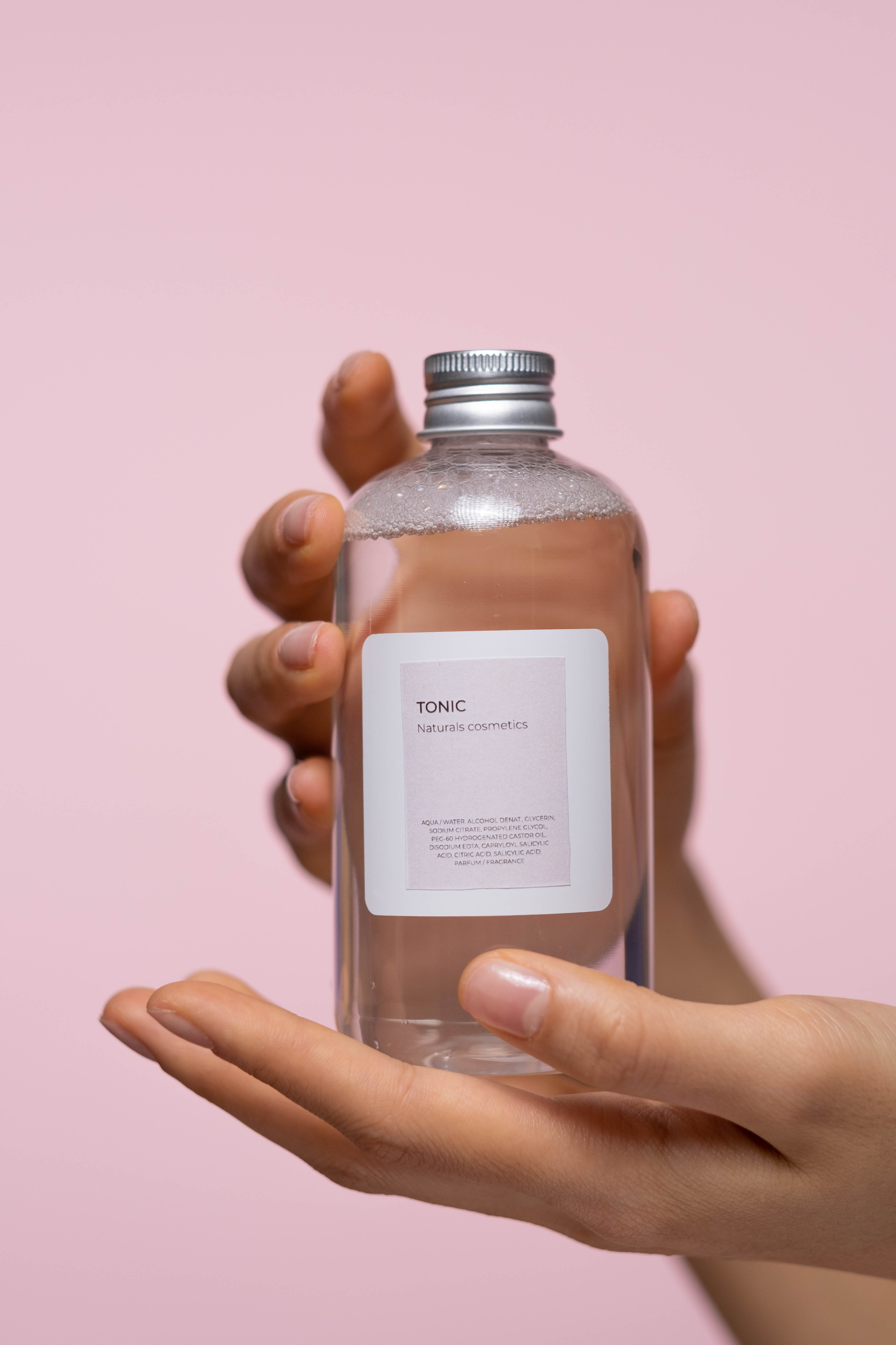 person holding a glass bottle with tonic