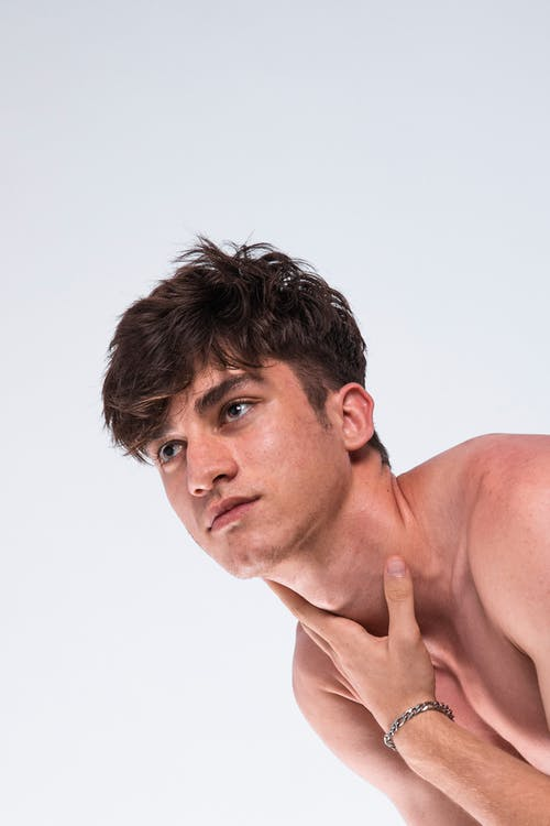 Handsome young shirtless guy touching neck in white studio