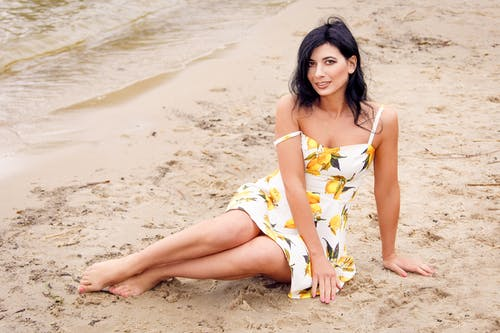 Woman in Yellow and White Floral Dress Sitting on Beach