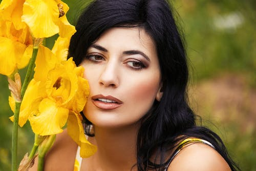 Woman in Black Tank Top Holding Yellow Flower