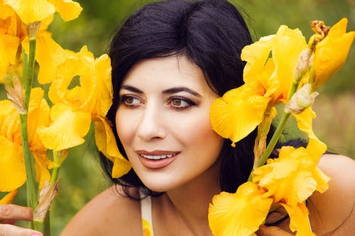 Woman in Yellow Sleeveless Top Holding Yellow Flower