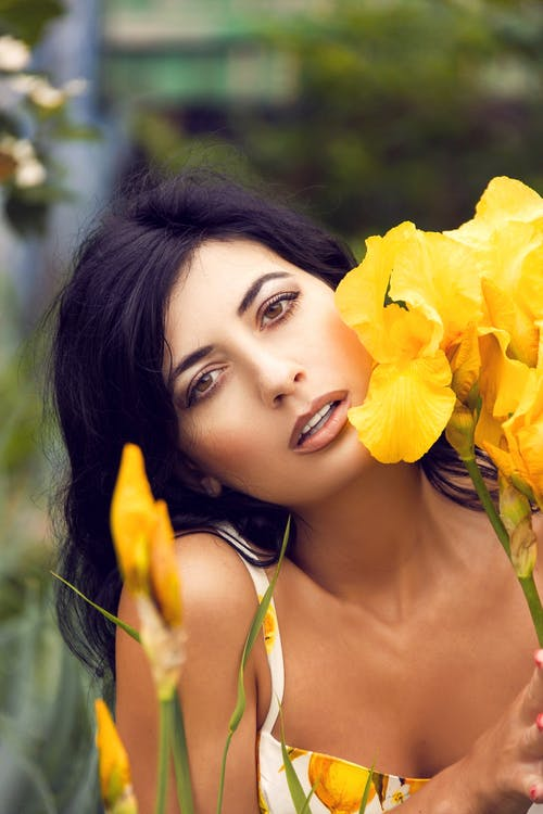 Woman in White Tank Top Holding Yellow Flower