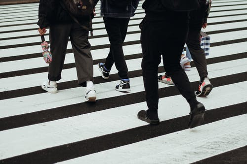 Crop unrecognizable people in casual clothes walking on wide asphalt road with pedestrian crossing in city in daytime