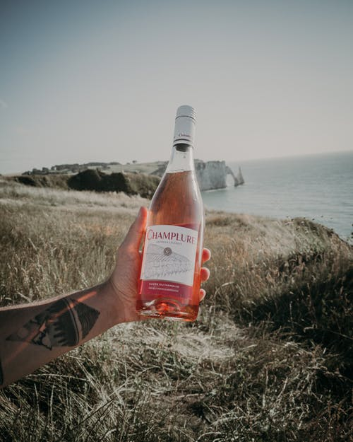 Crop man with bottle of champagne on shore
