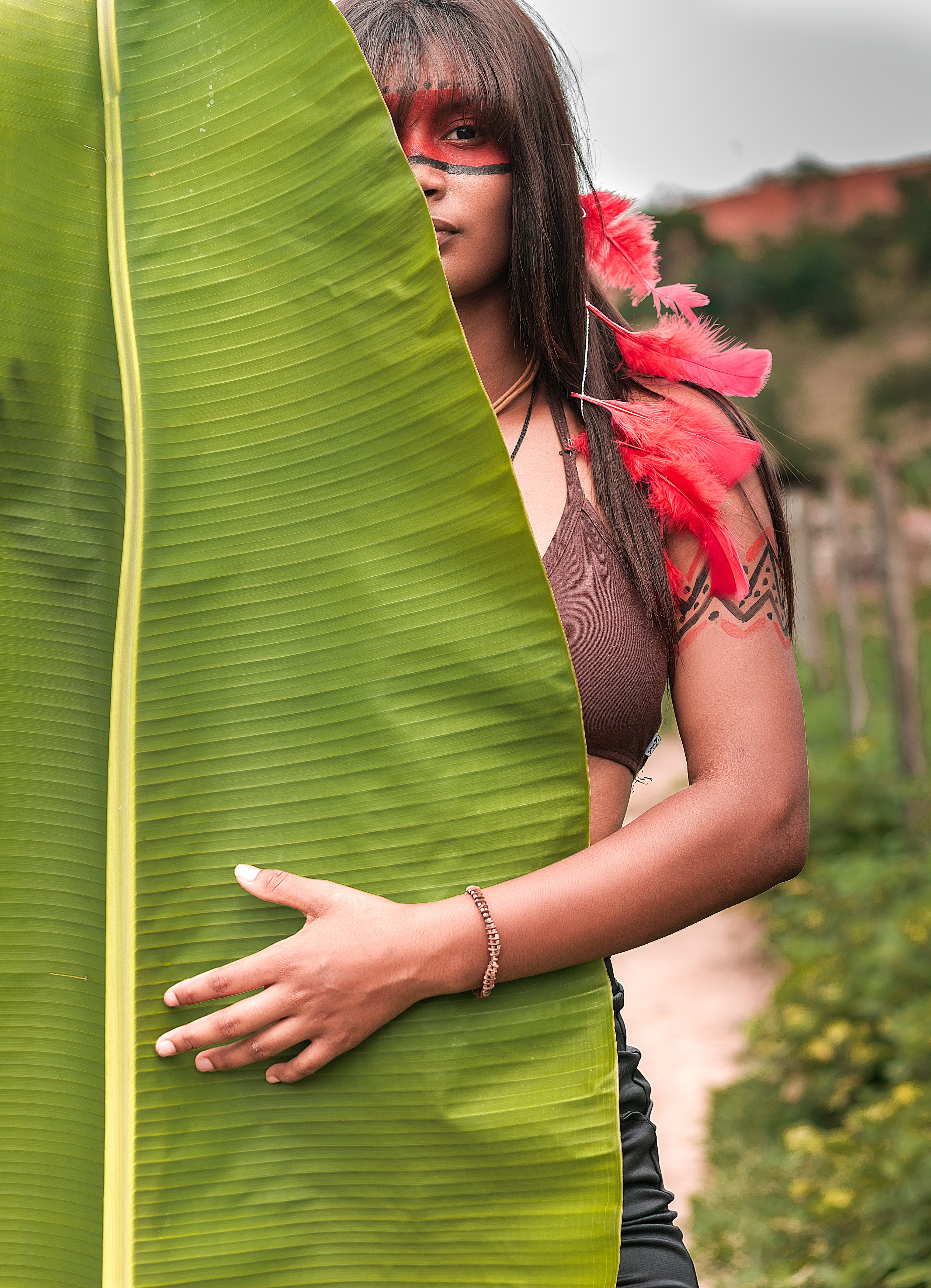 Woman in Brown Brassiere in Front of Banana Leaf