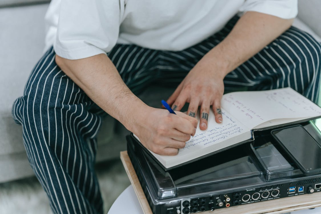 Man in Black and White Strip Pants Writing Notebook