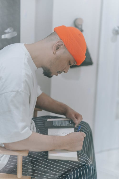 Man in White Shirt and Orange Cap Writing on Notebook
