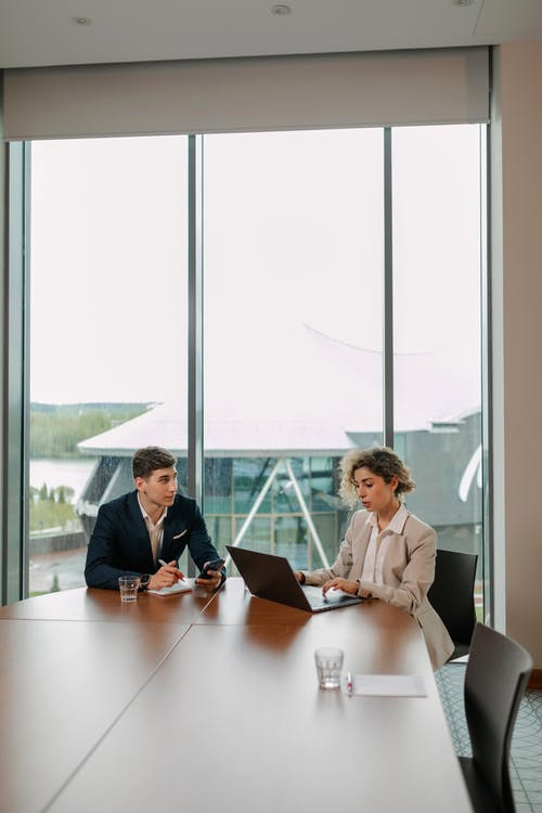 Two People Sitting at Table with Laptop Near the Window