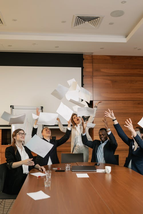 People Throwing Documents in a Meeting Room
