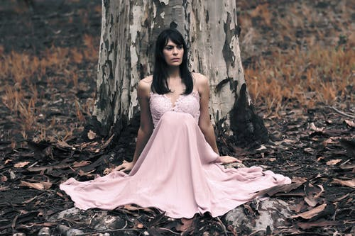Shallow Focus Photography of Black Haired Woman in Pink Sleeveless Dress Sitting in Front of Tree