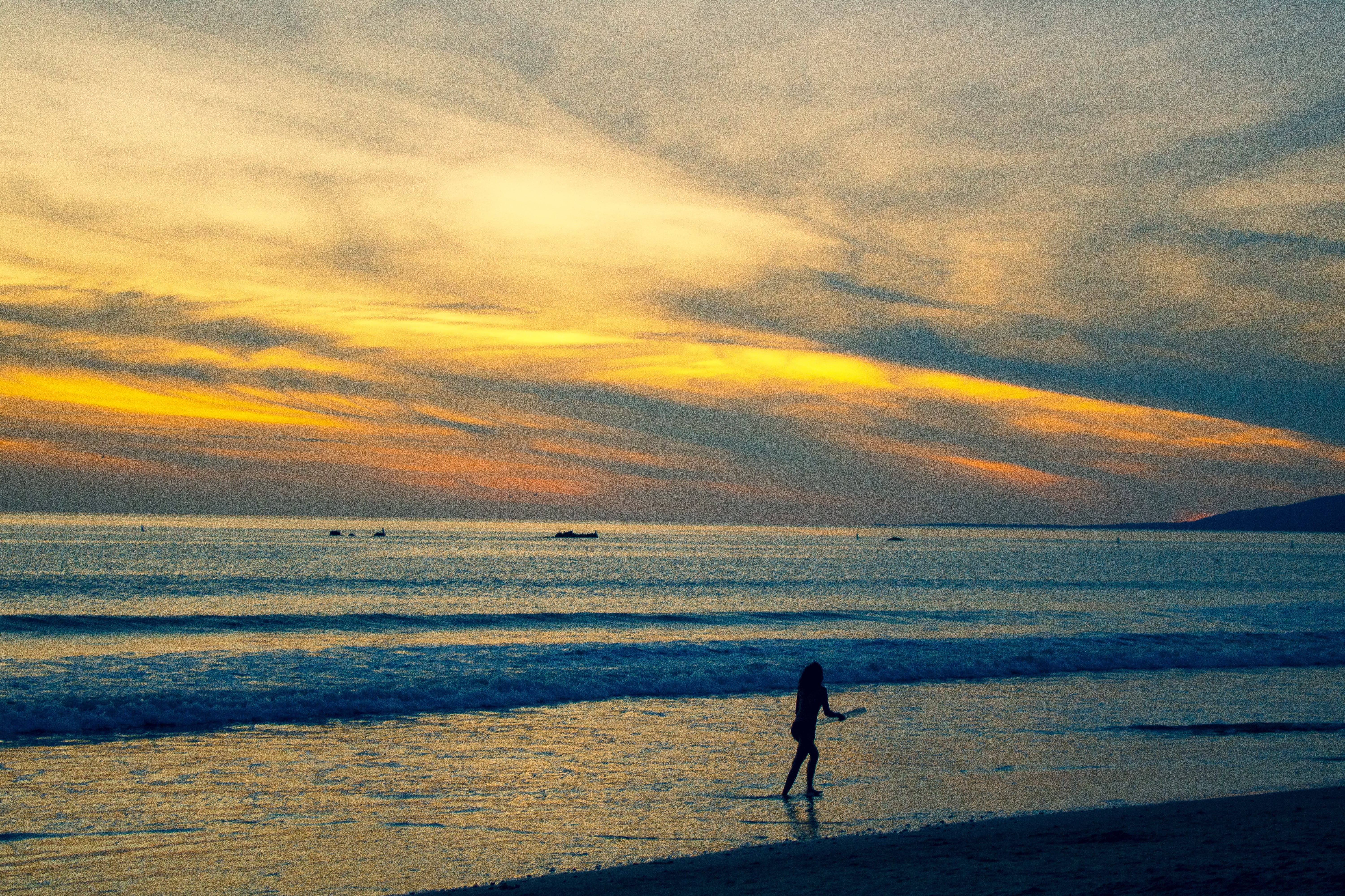 Photo of Person Walking on Beach Shore