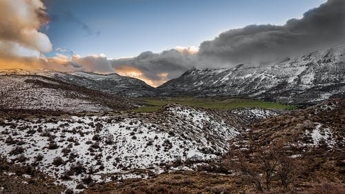 Scenic Photography of Mountains Covered With Snow Under Cloudy Sky