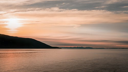 Silhouette of Mountain Beside Body of Water during Sunset