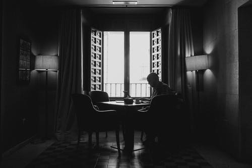 Silhouette Photography Of Man Sitting On Chair Beside Open Window